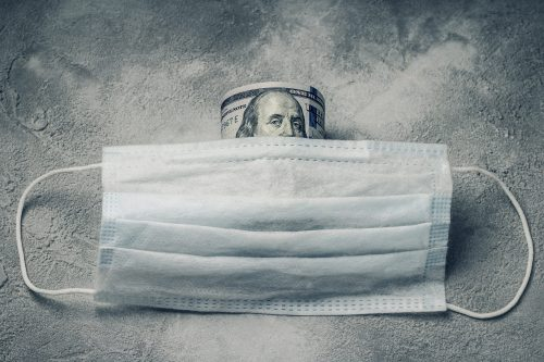 Medical mask and money . High price of masks and demand during quarantine .  Pile of anti virus surgical face masks and money.